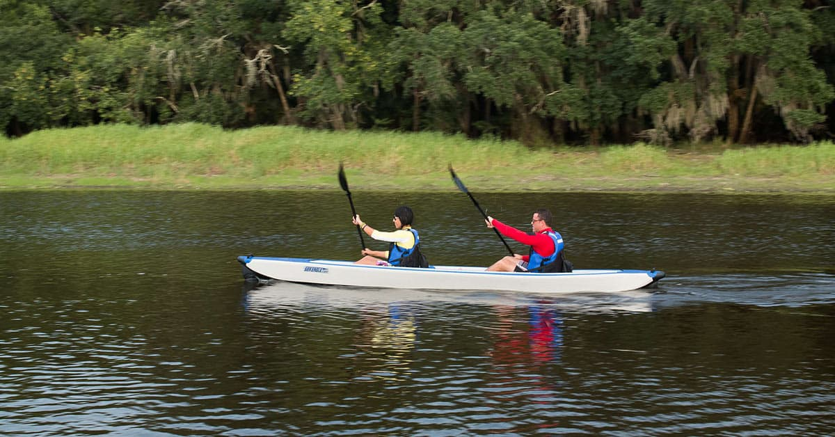 two kayakers speed through open water in a Sea Eagle 473rl RazorLite inflatable two-person kayak.