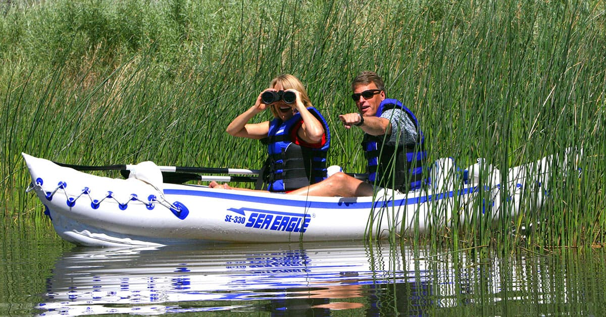 Two kayakers bird watching on a lake in a Sea Eagle 330 Sport Inflatable 2-Person Kayak.