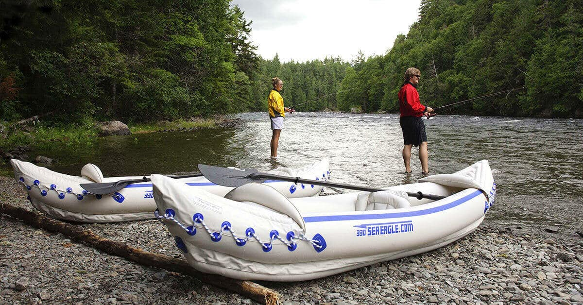 Two kayakers using Sea Eagle 330 Sport Inflatable Kayaks as solo kayaks stop to fish along a river's edge to fish.
