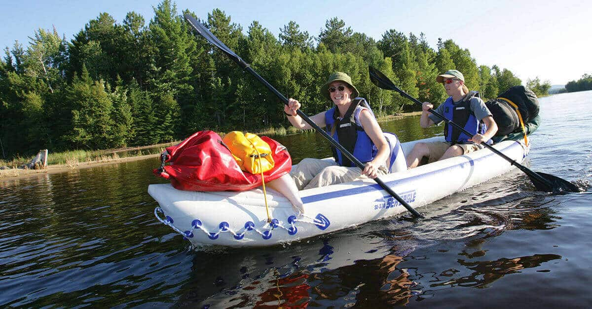 Paddlers tandem kayaking with camping gear in a Sea Eagle 370 Sport Inflatable Kayak 2-person kayak.