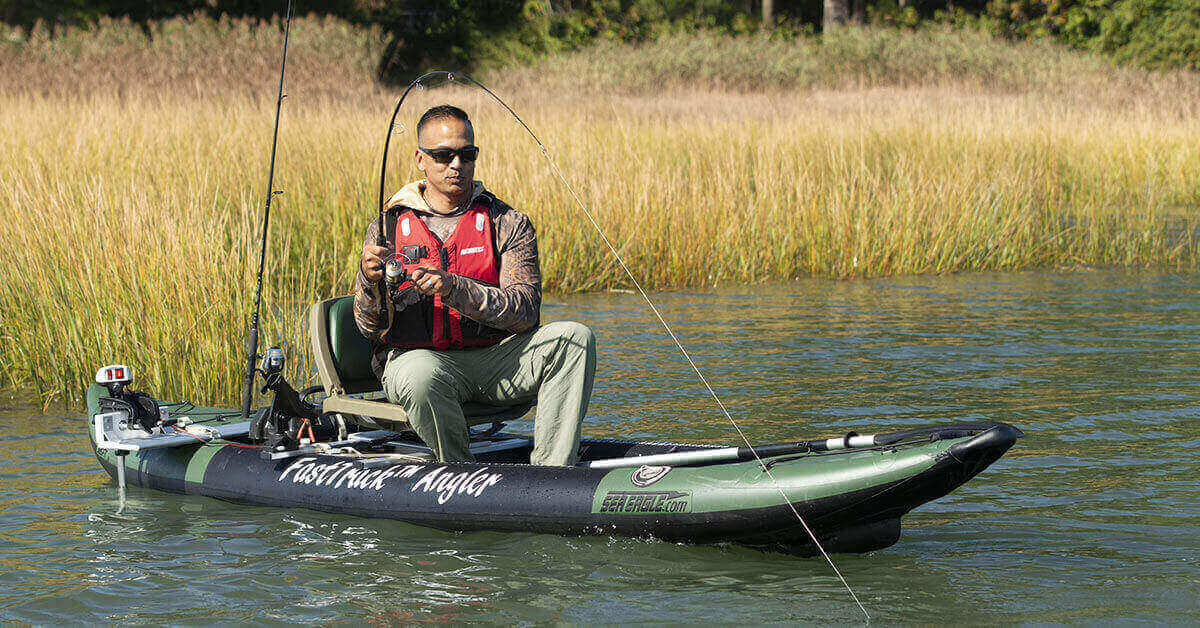 Fisherman reeling in a catch on a Sea Eagle 385fta FastTrack Angler inflatable kayak.