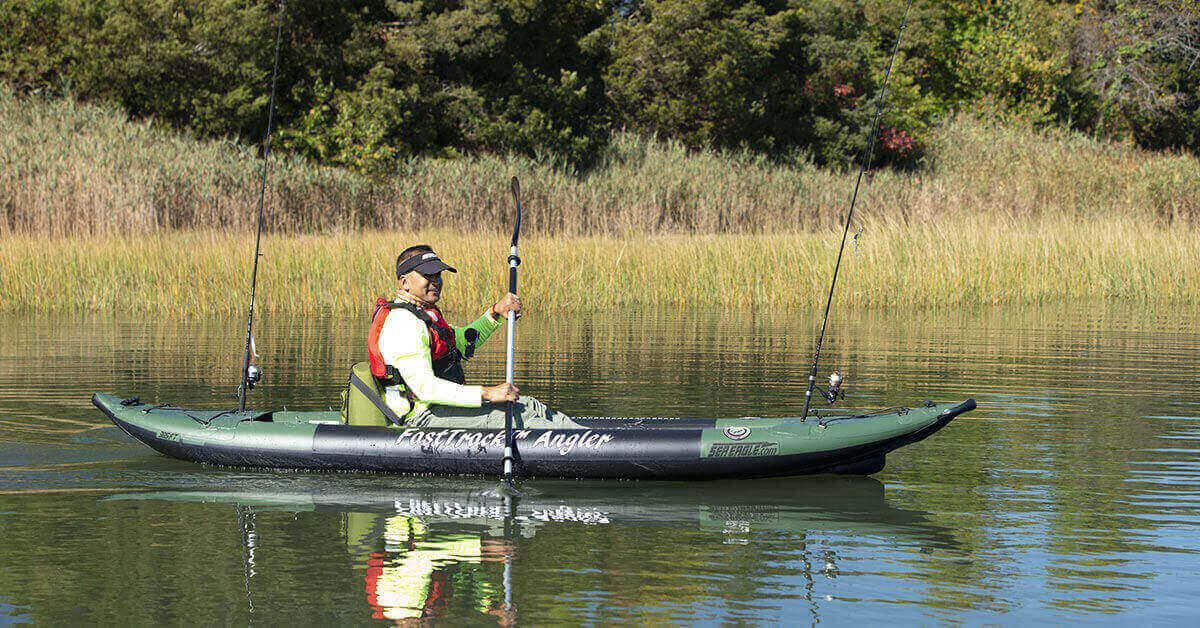 Fisherman paddling a Sea Eagle 385fta FastTrack Angler inflatable kayak on a lake.