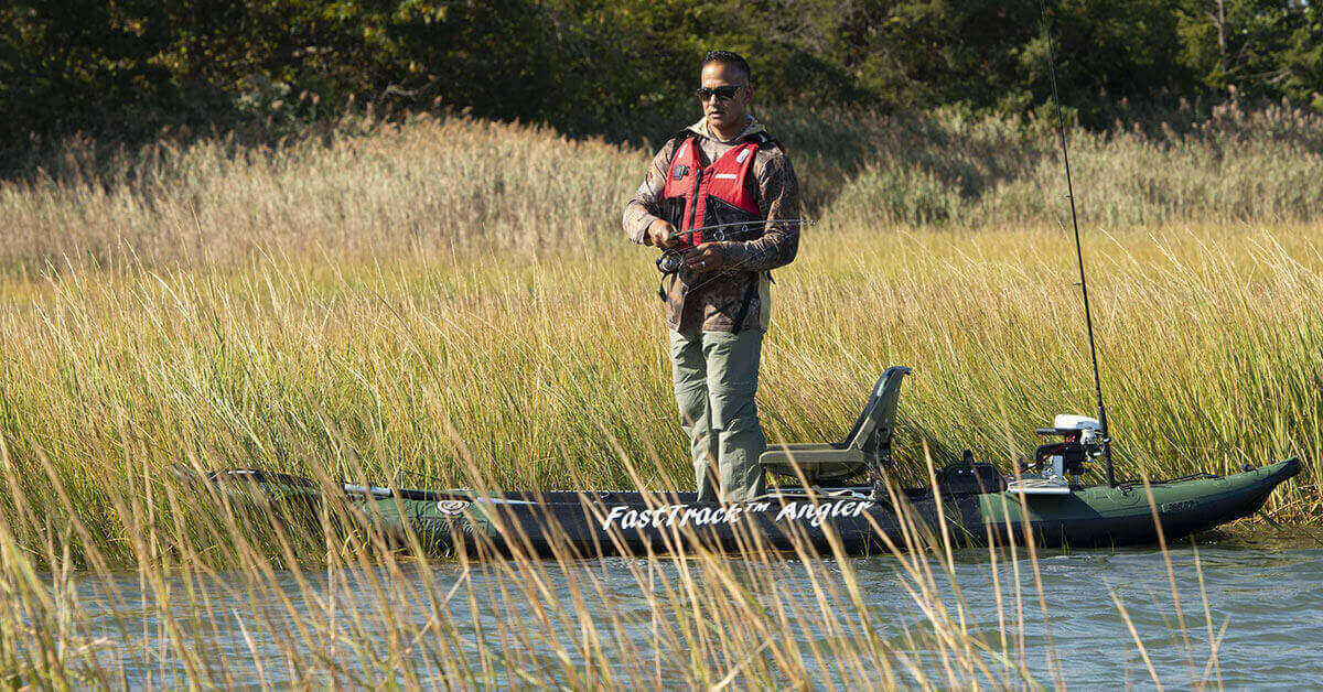 Fisherman standing up and fishing in a Stand Up Fishing in a Sea Eagle 385fta FastTrack Angler inflatable kayak.