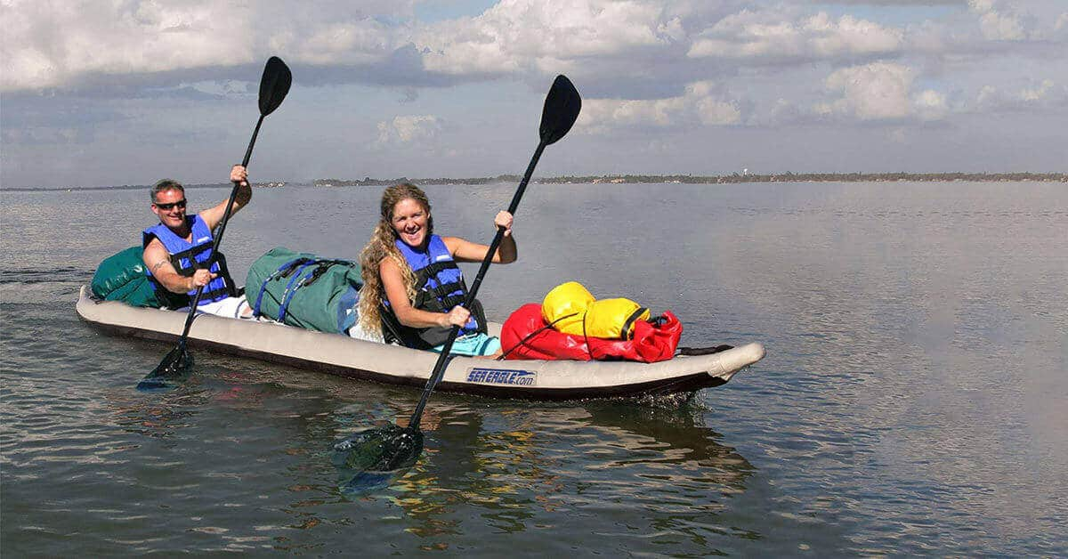 Two kayakers in a Sea Eagle 465ft FastTrack inflatable 2-person kayak loaded with camping gear.