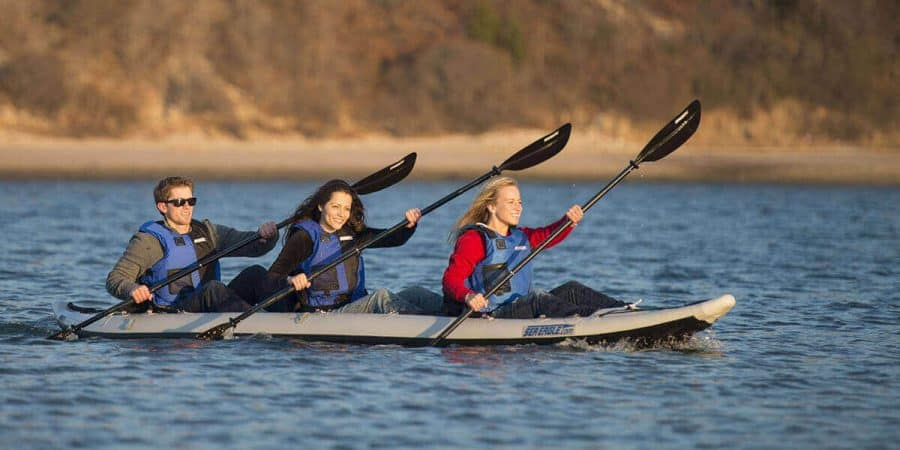 Three kayakers paddling a Sea Eagle 465ft FastTrack inflatable 3-person kayak on a lake.