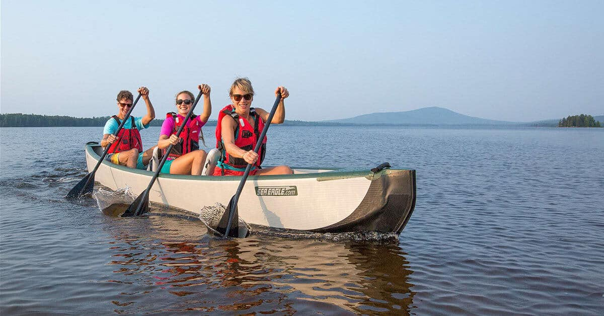Three women canoeing in a 3-person Sea Eagle Inflatable Travel Canoe 16.