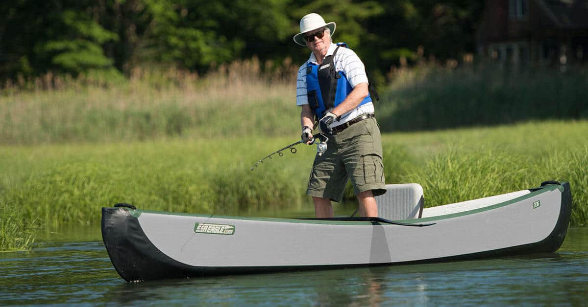A paddler stand-up fishing in a Sea Eagle Inflatable Travel Canoe 16.