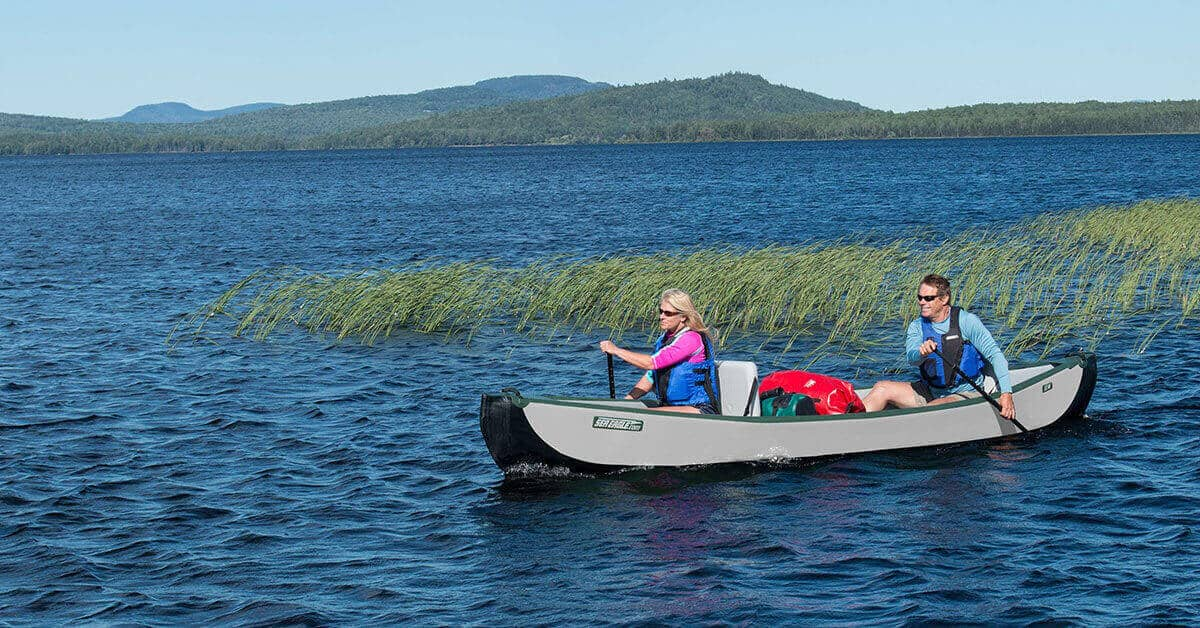 A two-person Sea Eagle Inflatable Travel Canoe 16 loaded with gear for lake camping.
