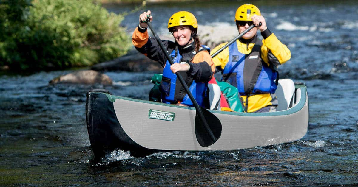 Two people paddling a Sea Eagle Inflatable Travel Canoe 16 on a river.