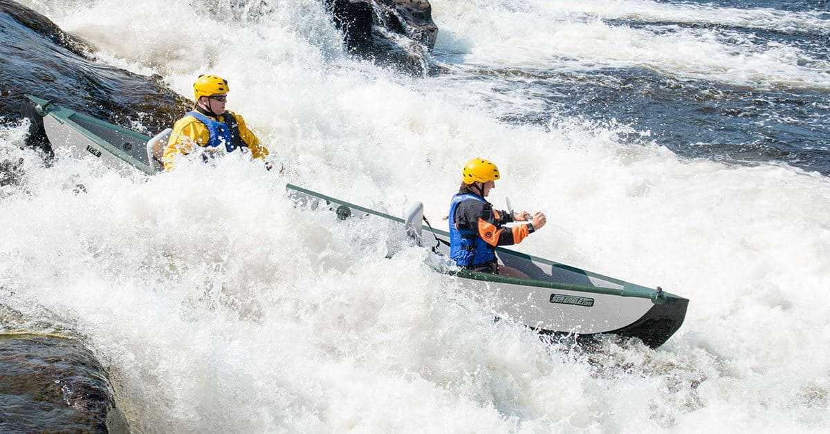 Two paddlers in a Sea Eagle Inflatable Travel Canoe 16 on a whitewater river ride.