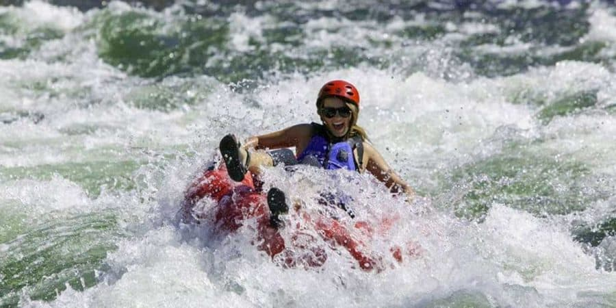 Woman riding an AIRE Rocktabomb inflatable river tube down a whitewater river.