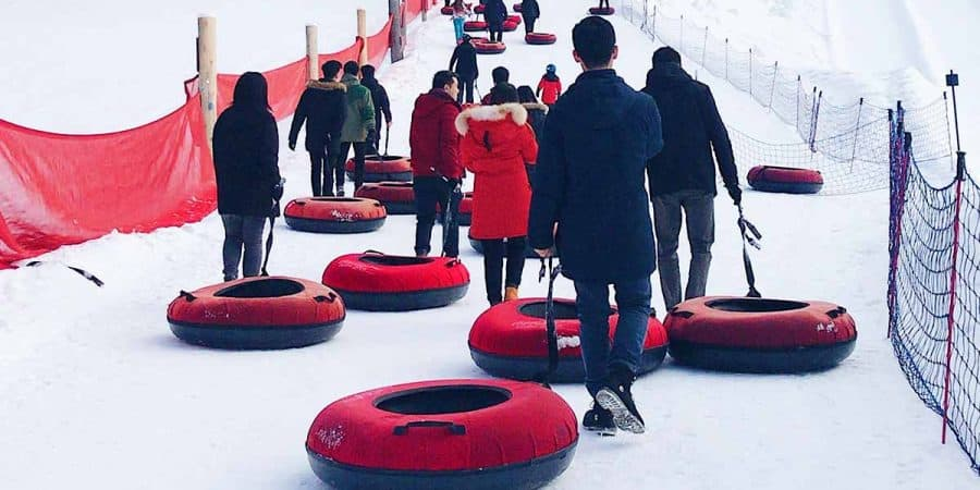 People sledding with heavy-duty snow tubes.