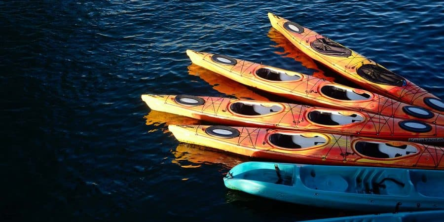 A group of sit-in 2-person kayaks and sit-on-top 2-person kayaks docked at a lake. Which of these tandem kayaks would be easier to paddle alone?