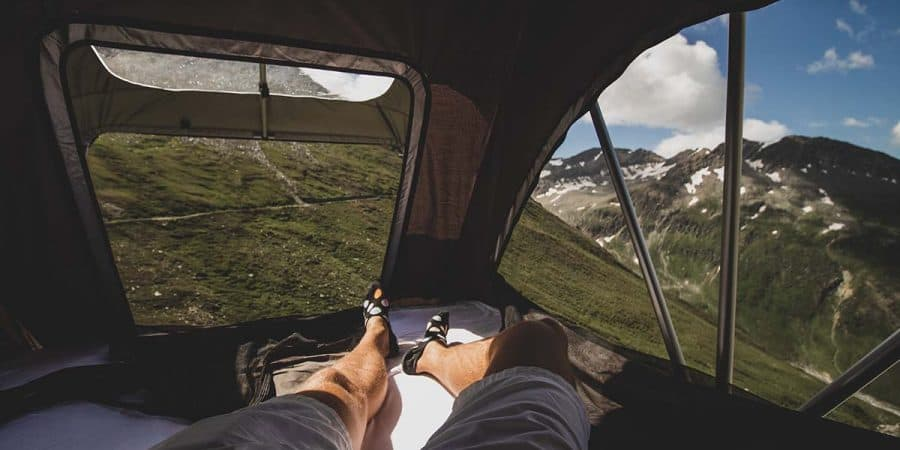 Laying in a leveled roof-top tent on a slope overlooking a mountain range and valley below.