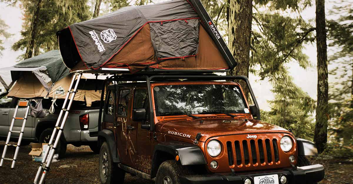 An iKamper hardshell roof-top tent on a Jeep Rubicon and a softshell tent mounted to a truck bed in the the woods on a camping trip.