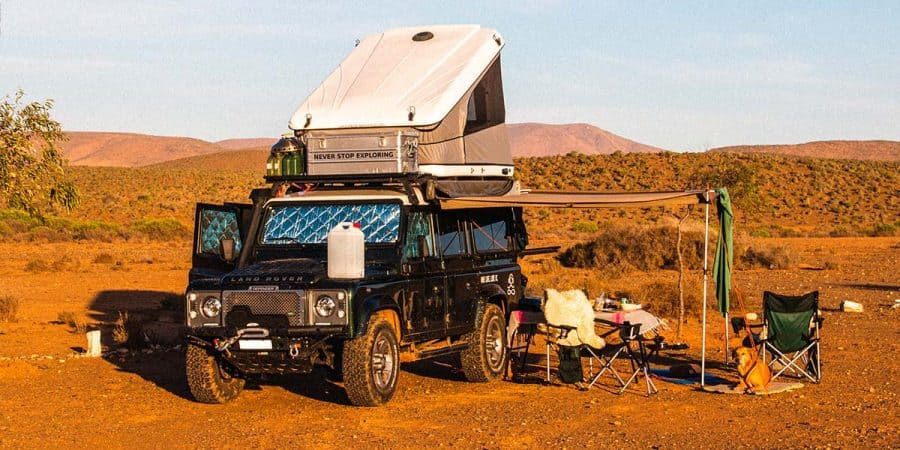 Camping with a hard shell roof-top tent on top of a Land Rover Defender.