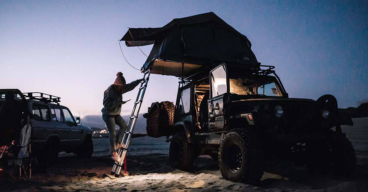 A roof-top tent on a Jeep Wrangler camping on a beach at night.