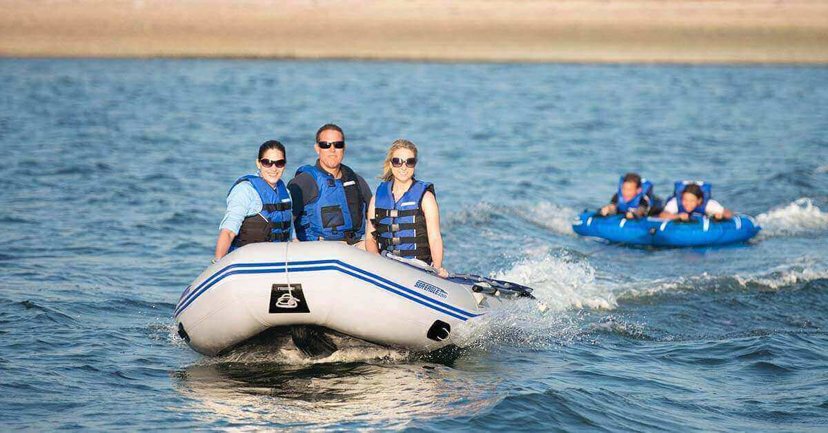 A Sea Eagle 12'6″ Sport Runabout Inflatable Boat pulling kids on a float.