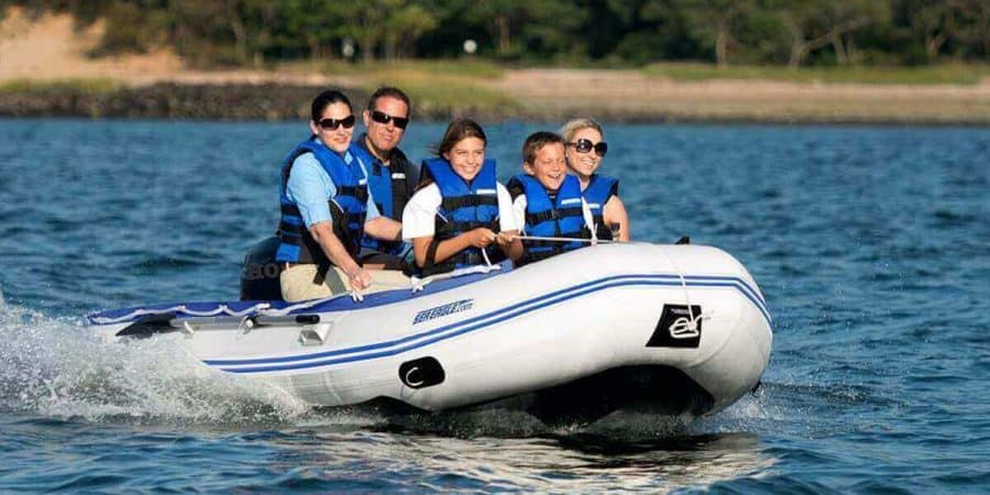 A Sea Eagle 12'6″ Sport Runabout Inflatable Boat with 5 passengers having fun on a bay.