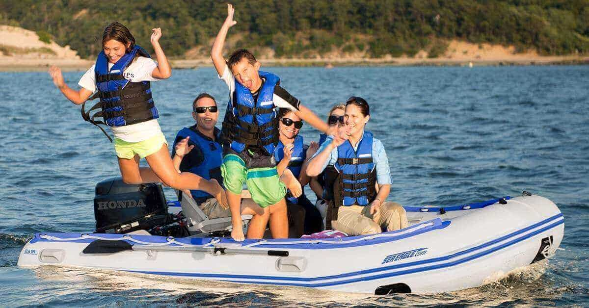 A Sea Eagle 12'6″ Sport Runabout Inflatable Boat with 6 passengers having fun in open water.