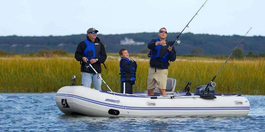 Two men and a boy fishing in a marsh from a Sea Eagle 14′ Sport Runabout Inflatable Boat.