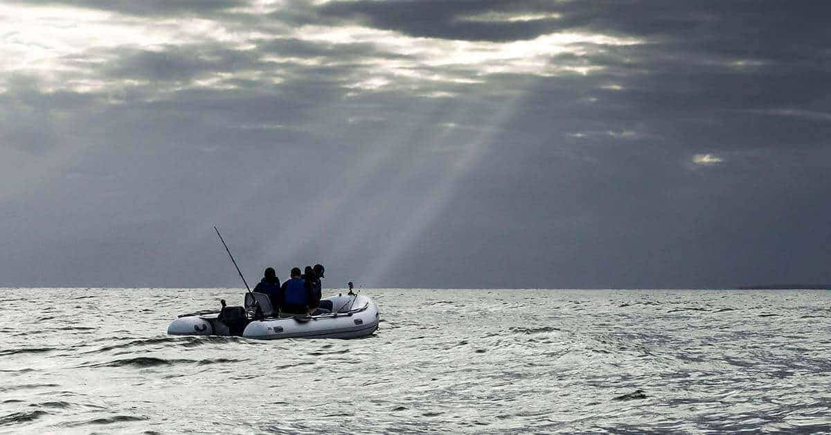 A Sea Eagle 14′ Sport Runabout Inflatable Boat out on the ocean on a stormy day.