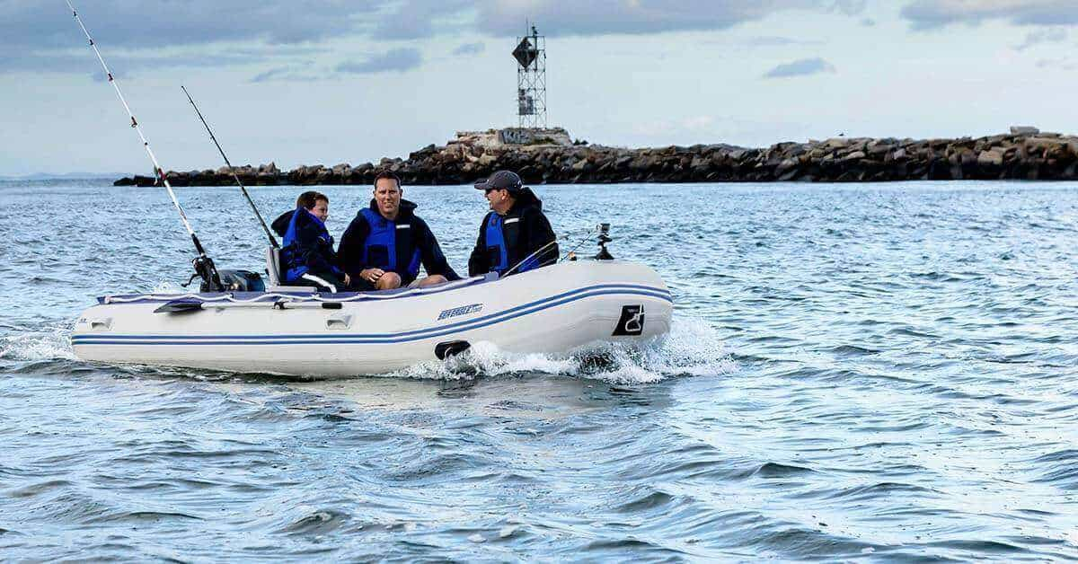 Two men and a boy sea fishing in a Sea Eagle 14′ Sport Runabout Inflatable Boat.