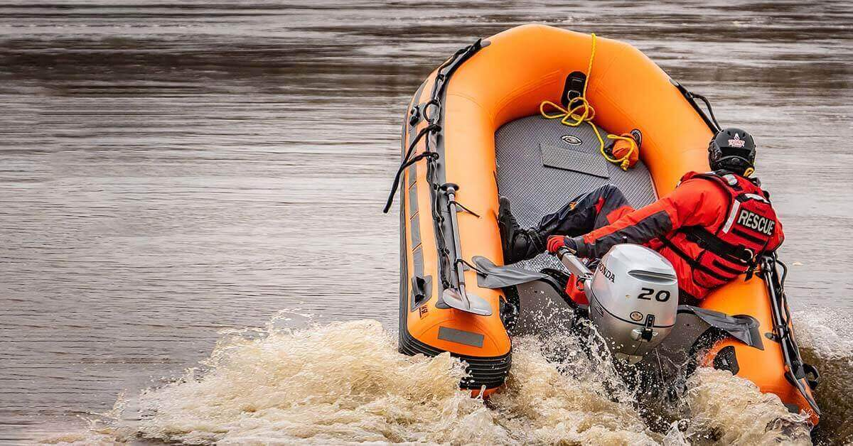 A Sea Eagle Rescue14 Sport Runabout Inflatable Boat with a 20hp motor taking off at top speed.