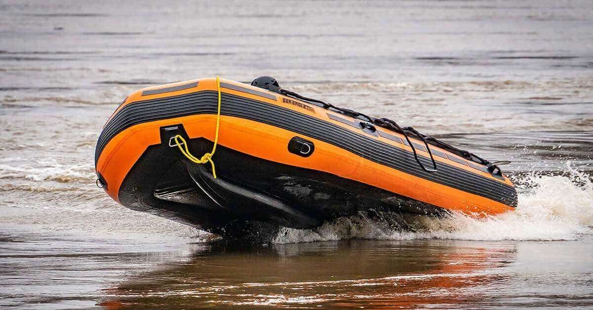 A Sea Eagle Rescue14 Sport Runabout Inflatable Boat racing at top speed through river currents.