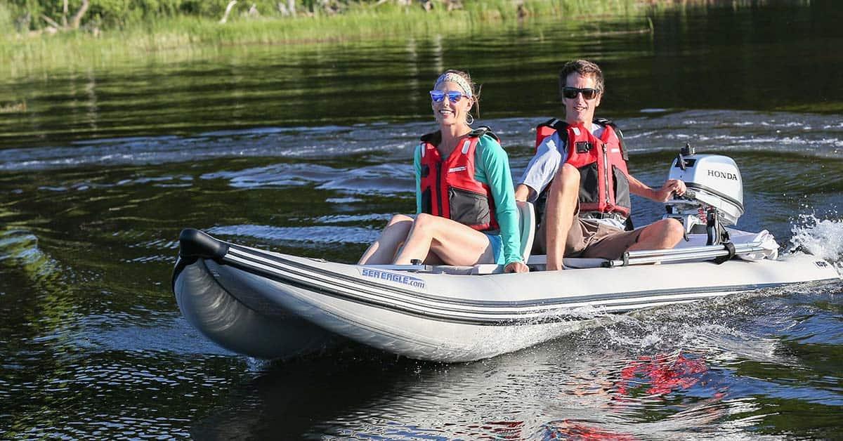 Two people using a Honda outboard motor on a Sea Eagle 437ps PaddleSki Inflatable Tandem Catamaran-Kayak-Boat.