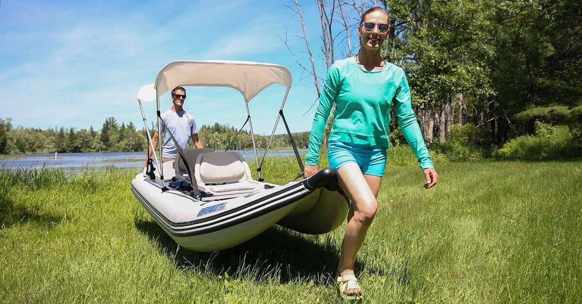 Two people carrying a Sea Eagle 437ps PaddleSki Inflatable Tandem Catamaran-Kayak-Boat with its grab handles.