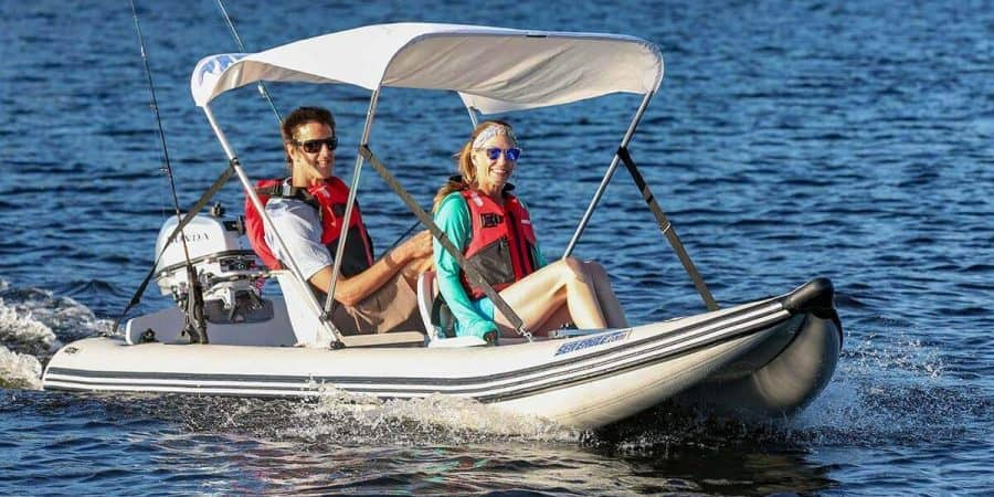 Two people using a Honda outboard motor on a Sea Eagle 437ps PaddleSki Inflatable Tandem Catamaran-Kayak-Boat with a canopy.
