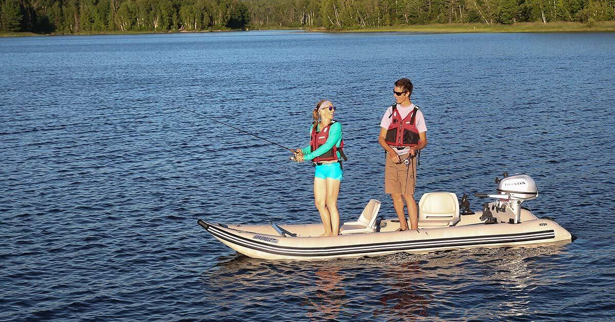 Two people standing up in and fishing from a Sea Eagle 437ps PaddleSki Inflatable Tandem Catamaran-Kayak-Boat.