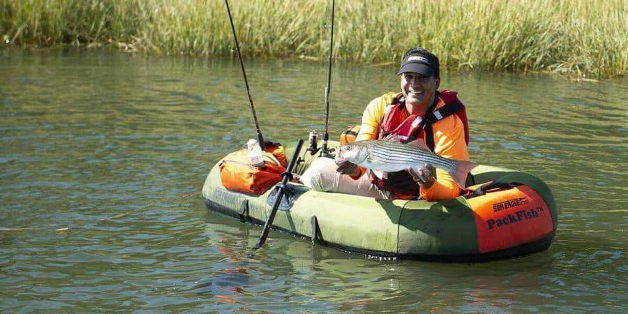 Fisherman showing off a catch made from a Sea Eagle PackFish7 inflatable boat.