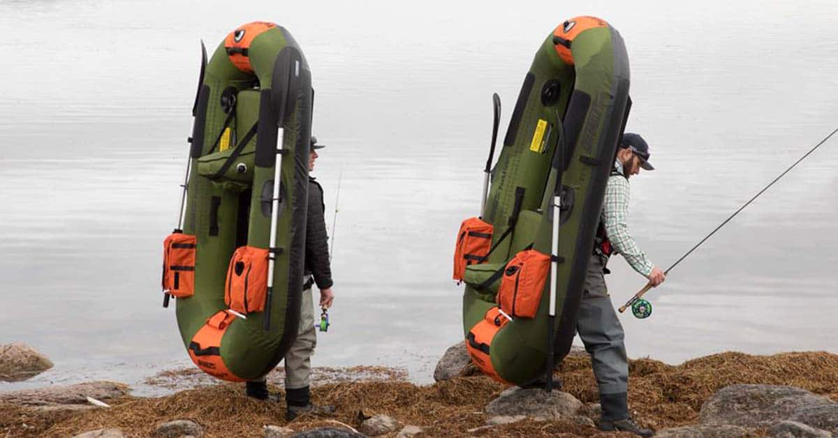 Fly fishermen walking to a put-in each with a Sea Eagle PackFish 7 strapped to their backs like an oversized backpack.